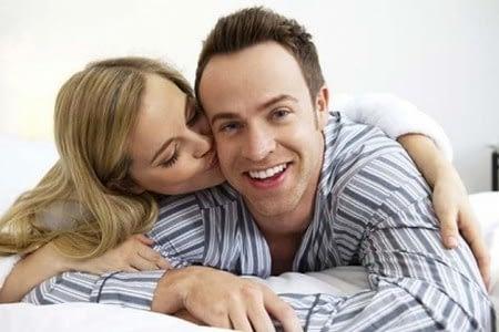 Женщина целует счастливого мужчину