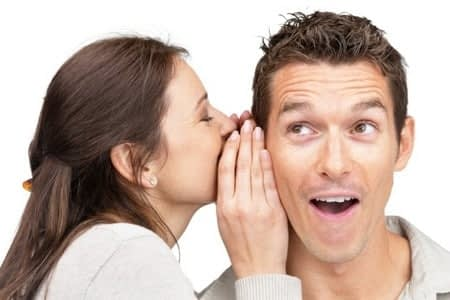 Женщина говорит на ухо мужчине