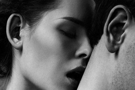 Женщина целует мужчину в шею