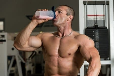 Мускулистый мужчина пьет