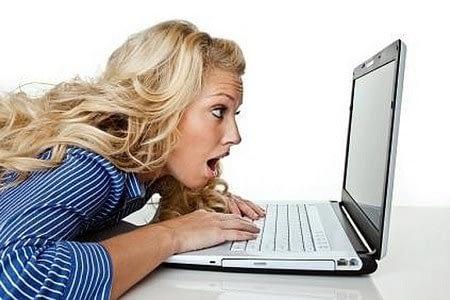 Женщина с открытым ртом смотрит в ноутбук