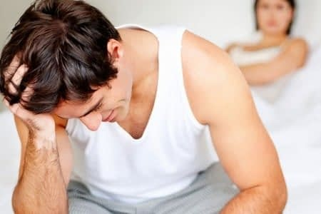 Мужчина сидит на кровати склонив голову