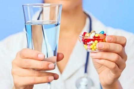 Врач с таблетками и стаканом воды