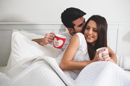 мужчина и женщина пьют кофе в постели